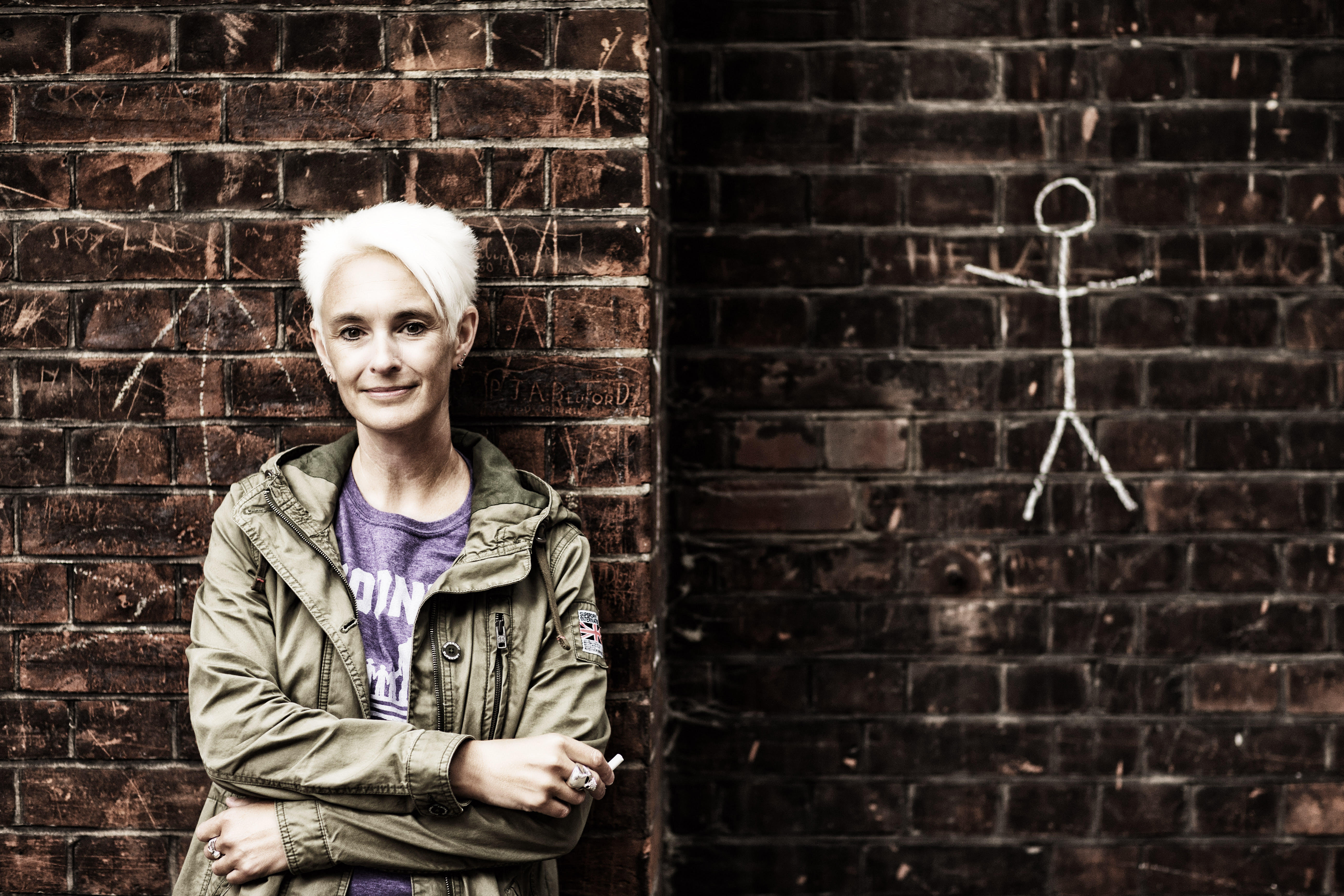 A picture of the interviewee in front of a wall with a man drawn in chalk on it