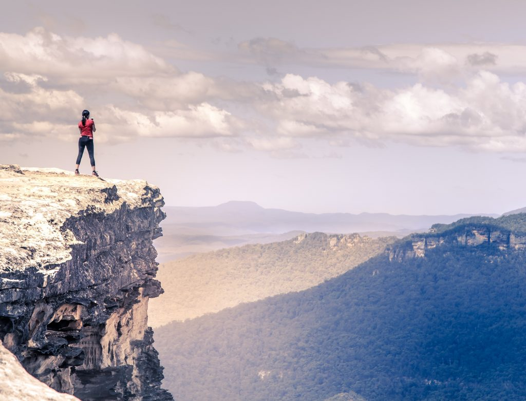 A picture of a person stood at the edge of a cliff