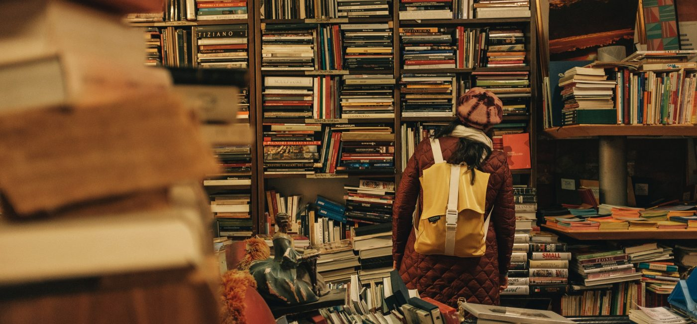 A picture of someone with their face in a bookshelf