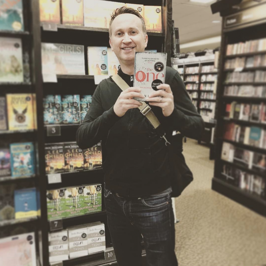 A picture of John holding his book