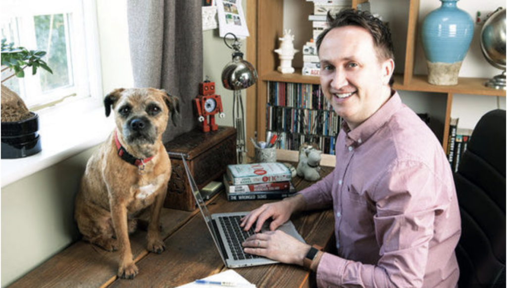 A picture of John Marrs at his desk with his dog