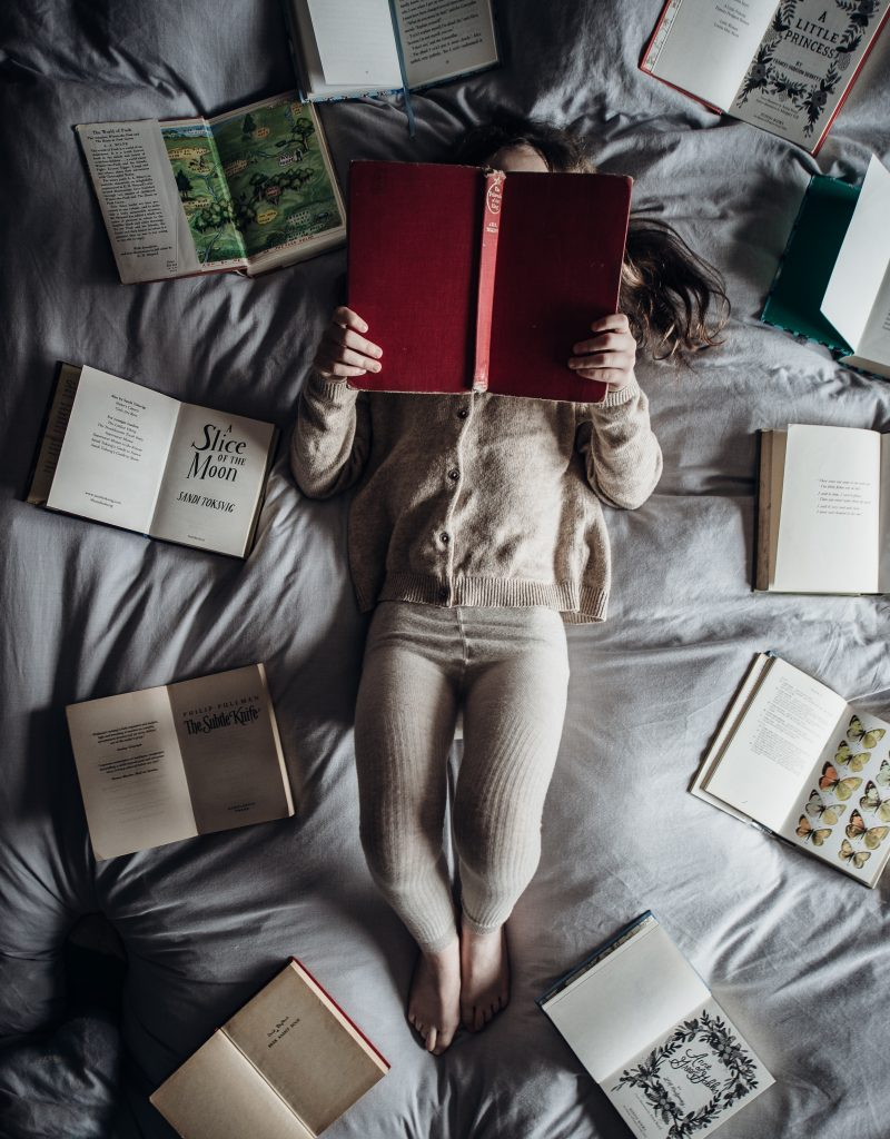 A picture of a person laying on a bed with their face in a book