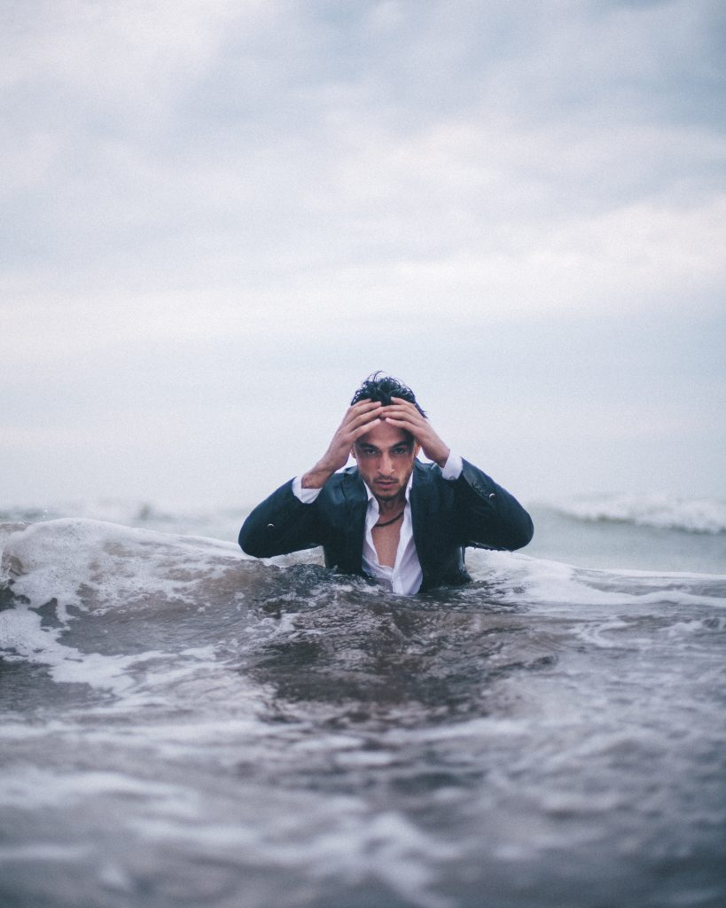 A picture of a fully dressed man in the sea