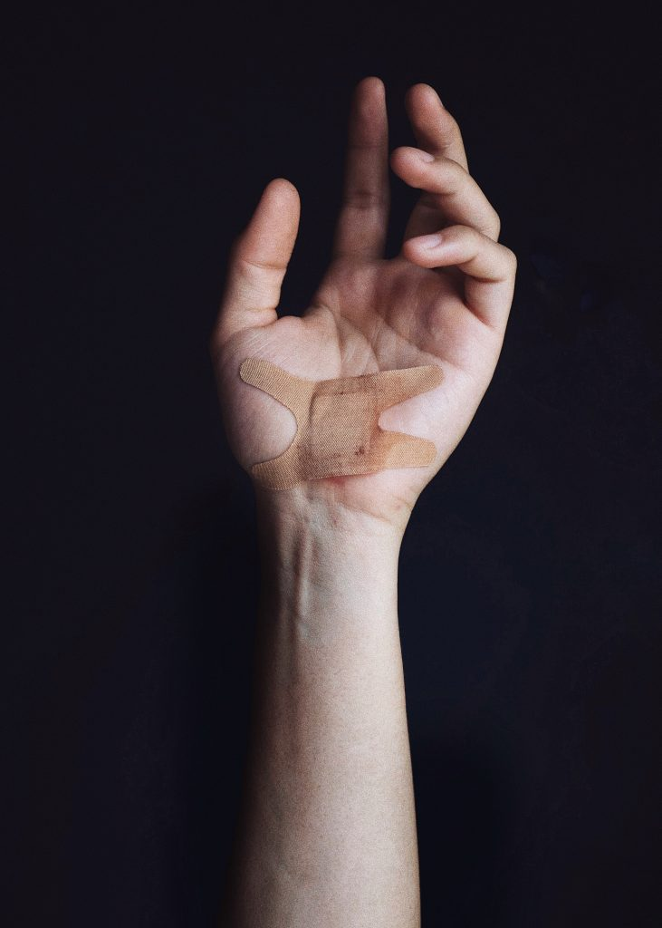 A picture of an arm with a plaster over a wound.