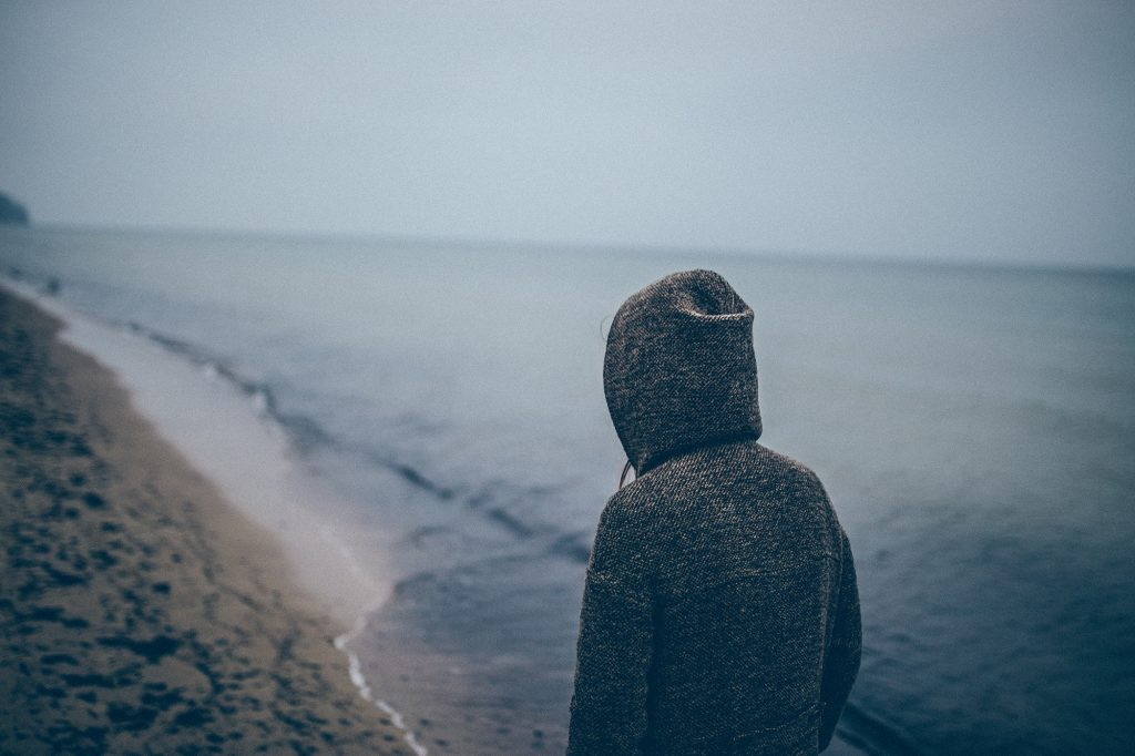 A picture of a depressed looking person on a dark beach