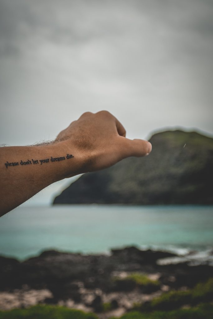 A picture of someone reaching out with a tattoo.